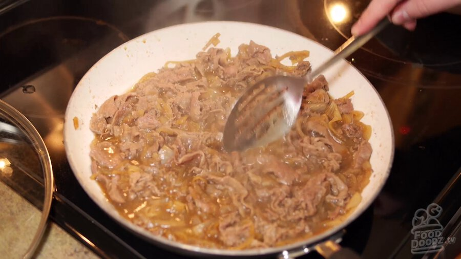 Large slotted spoon stirs beef, onion, sauce mixture in skillet while steam rises