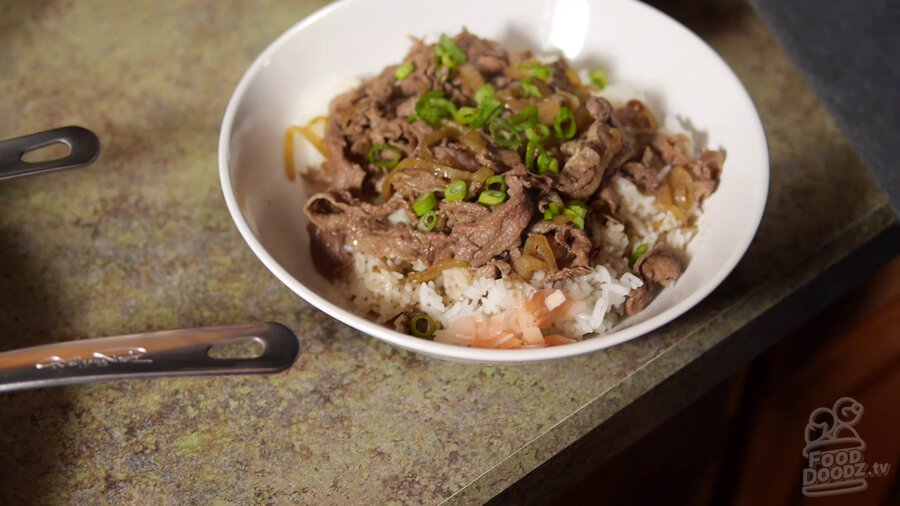 Finished and plated Japanese gyudonburi (beef rice bowl) sits on counter topped with sliced green onion and a side of pickled ginger waiting on a hungry dood to come and chow down. Looks delicious!