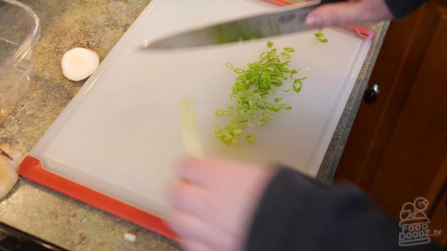 Green onion is sliced on cutting board