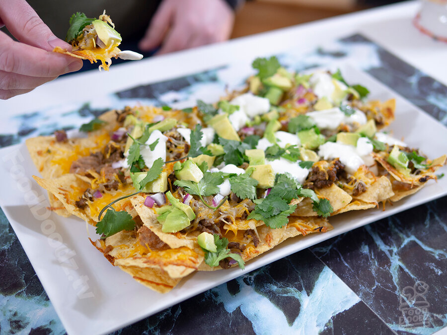 Gigantic rectangular plate of ultimate nachos sits on top of colorful background while hand holds a tasty bite above plate