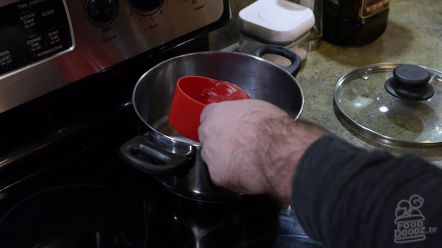 Water is added to sauce pan using measuring cup