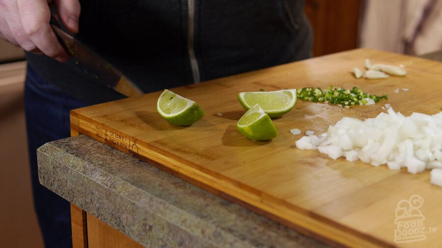 Limes are cut into slices on wooden cutting board