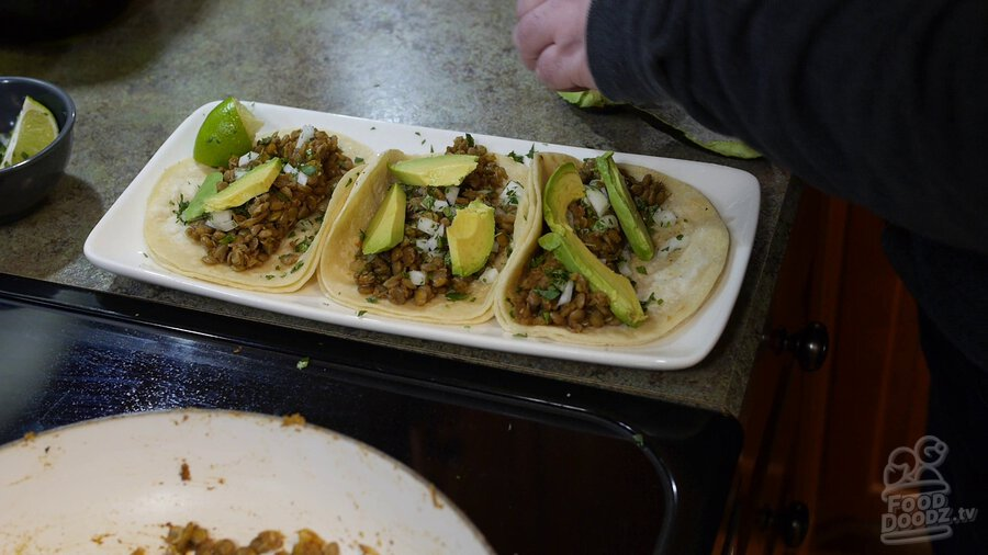 Delicious plate of lentil tacos is assembled with slices of avacado and chopped cilantro on top. Yum!