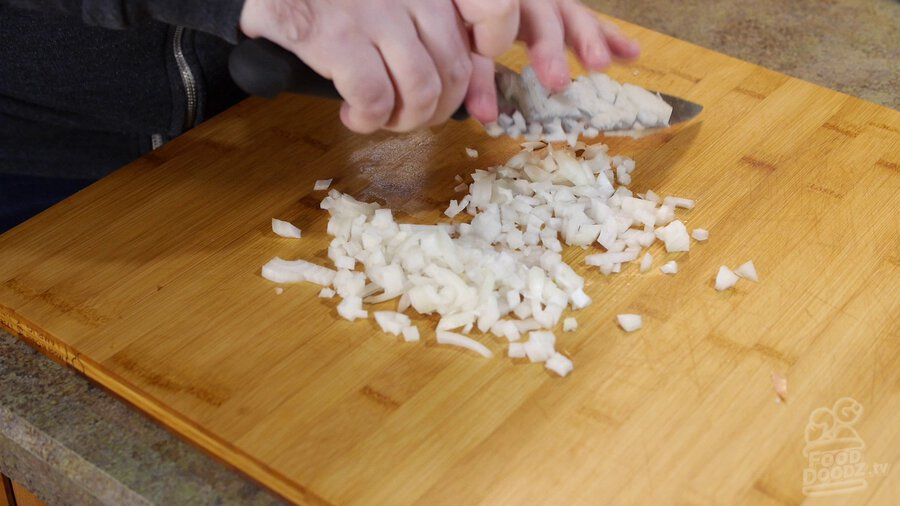 Onion is chopped with chef's knife on wooden cutting board