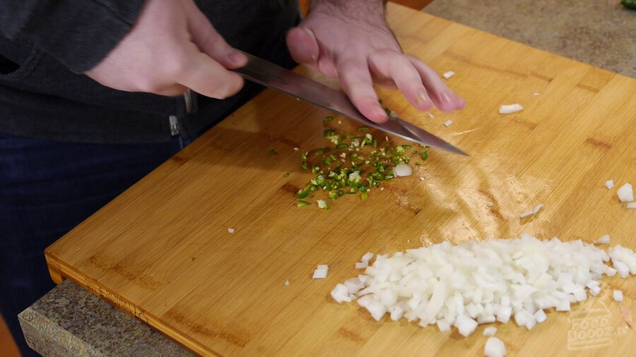 Serrano is chopped with chef's knife on wood cutting board