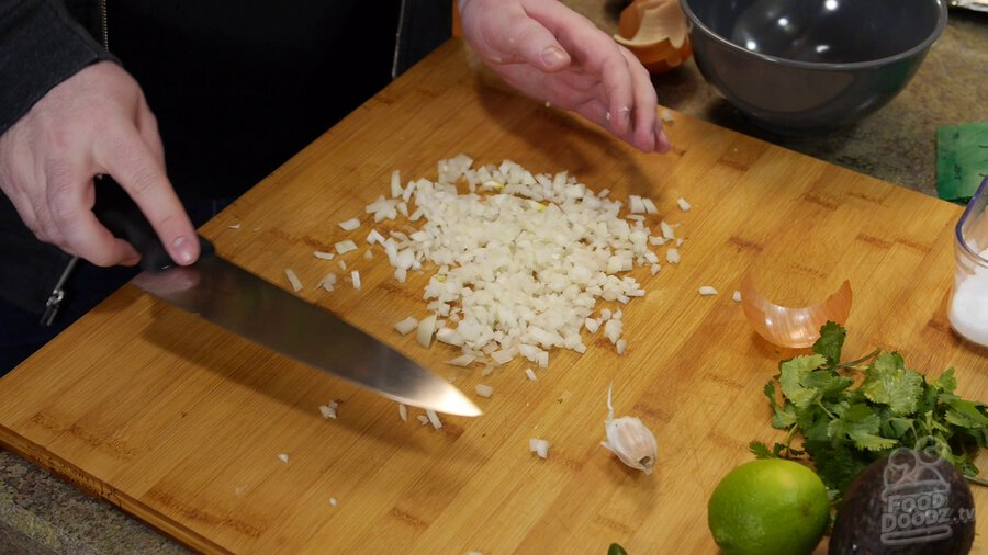 Chopped onion sits on wooden cutting board. Garlic, lime, avocado, and cilantro can be seen nearby.