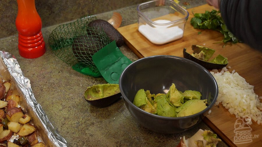 Avocado is removed from casing and added to bowl.