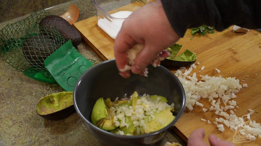 Adding onion and serrano peppers to bowl of avocado chunks.