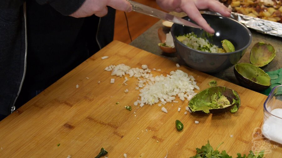Using chef's knife serrano is scooped up and placed in bowl with avocado and onion.