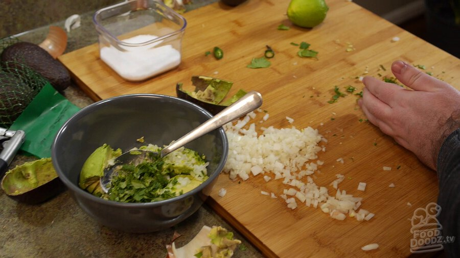 Finely chopping cilantro on wooding cutting board and adding it to bowl with avocado, onion, and serrano peppers.