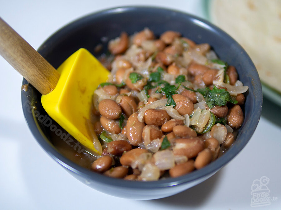 Juicy bowl of spicy Mexican pinto beans sits with serving spoon resting in it. Bits of cilantro, onion, and serrano pepper and be seen.