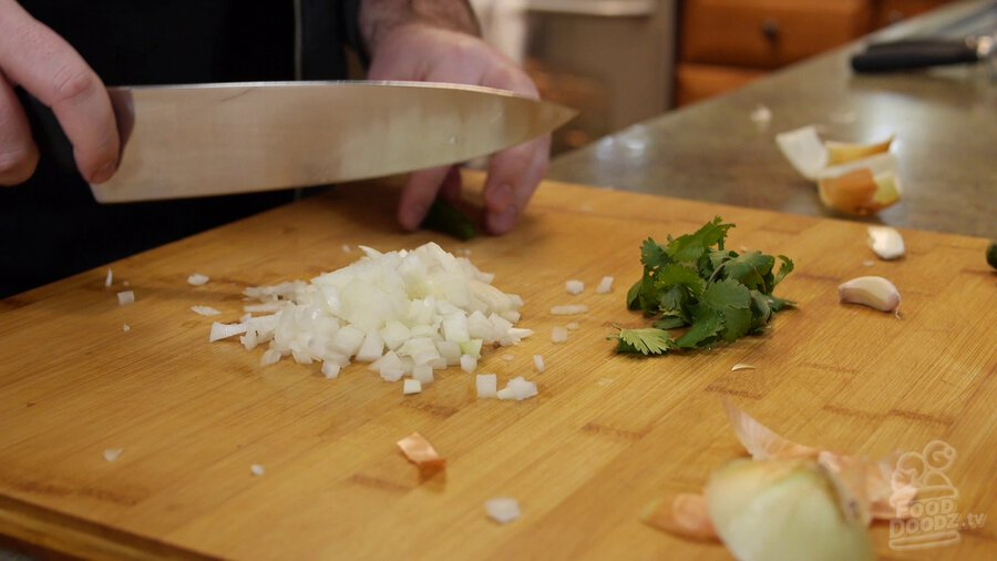Onion sits chopped on cutting board next to a bunch of cilantro, while serrano pepper gets sliced