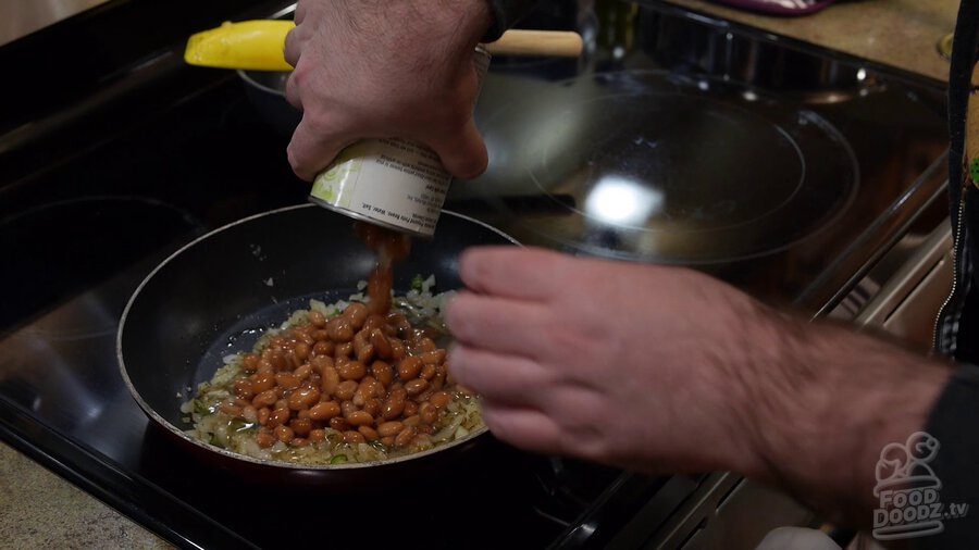 Can of pinto beans is added to skillet with onions and serrano peppers