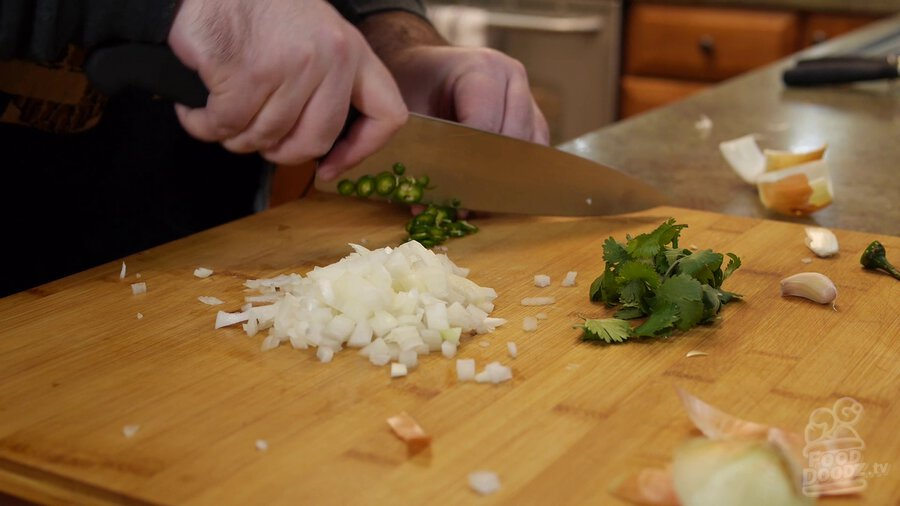 Chef's knife slicing up serrano pepper on cutting board. Chopped onion and a bunch of cilantro can be seen in the foreground.