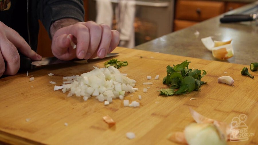 Using side of chef's knife and bottom of hand to pound down garlic and release it from its wrapper