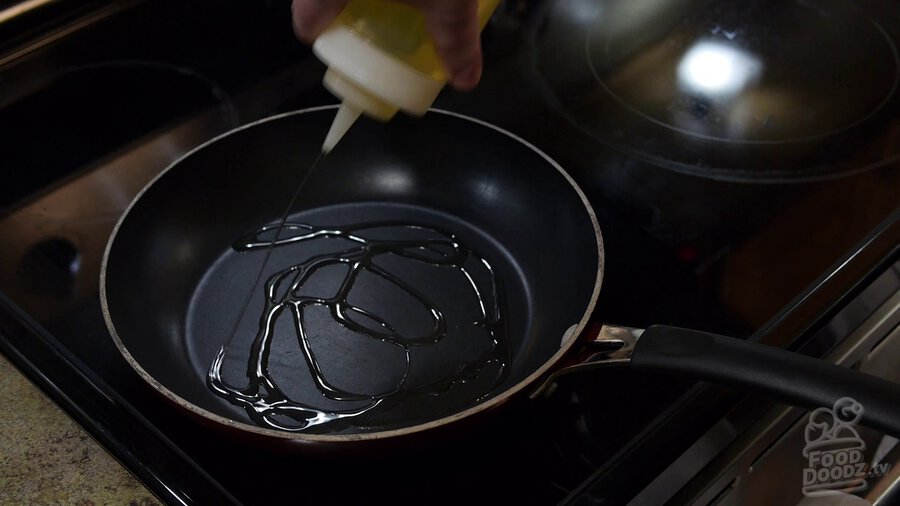 Using squirt bottle to add vegetable oil to non-stick skillet, coating bottom