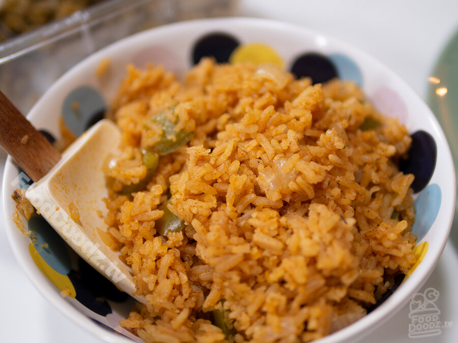 Tasty looking bowl of mexican rice with green bell peppers, onions, and tomatoes sits with large serving spoon to one side.