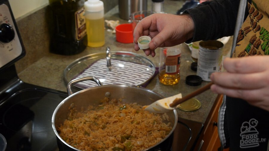 Vinegar is carefully added using the bottle cap to finished Mexican rice. It looks delicious!