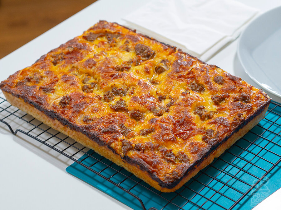 Absolutely beautiful golden brown sheet pan pizza resting on baking rack to cool. There's a nice caramelized cheese ring around the edge of the crust. The pie is topped with spicy Italian sausage, pepperoni, cheese blend, and onions. Yum!
