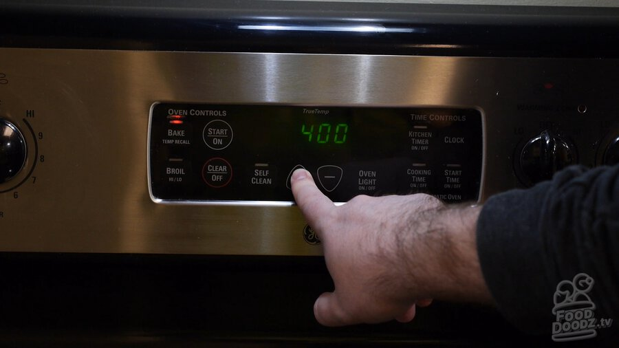 Hand presses button on oven control panel setting it to 400 degrees