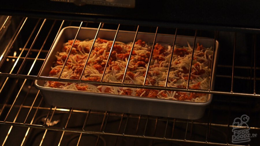 Unbaked pan pizza sits in middle rack of oven