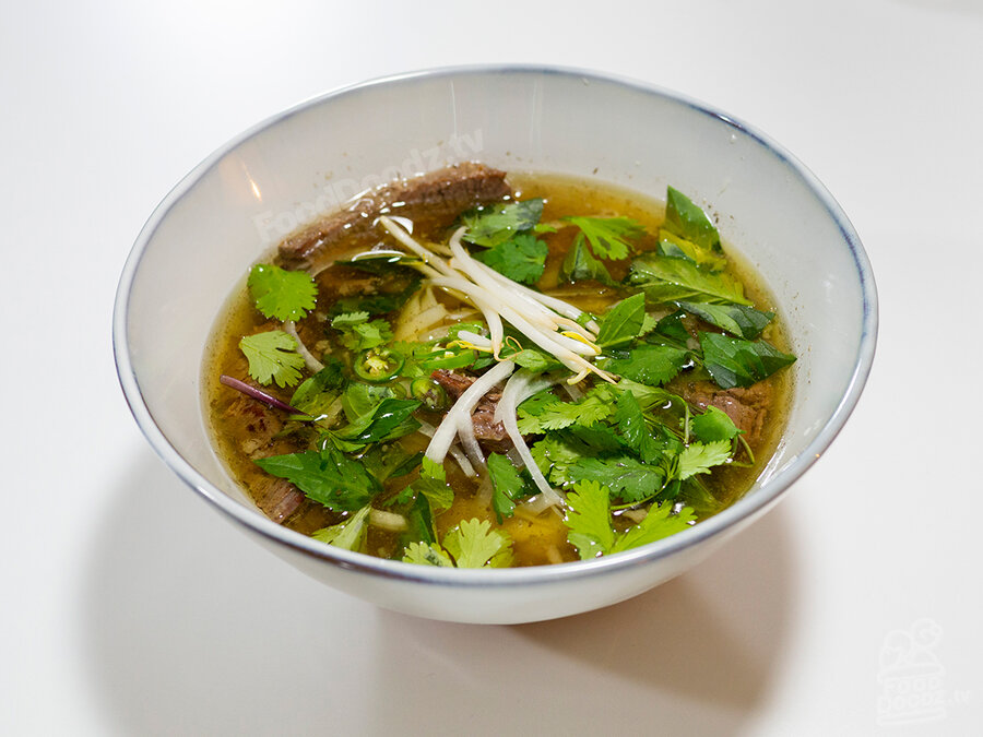 Gigantic bowl of fresh homemade Vietnamese Pho Beef Noodle Soup made from scratch in an Instant Pot with bone broth and topped with beansprouts, cilantro, sliced serrano chili peppers, and Thai basil
