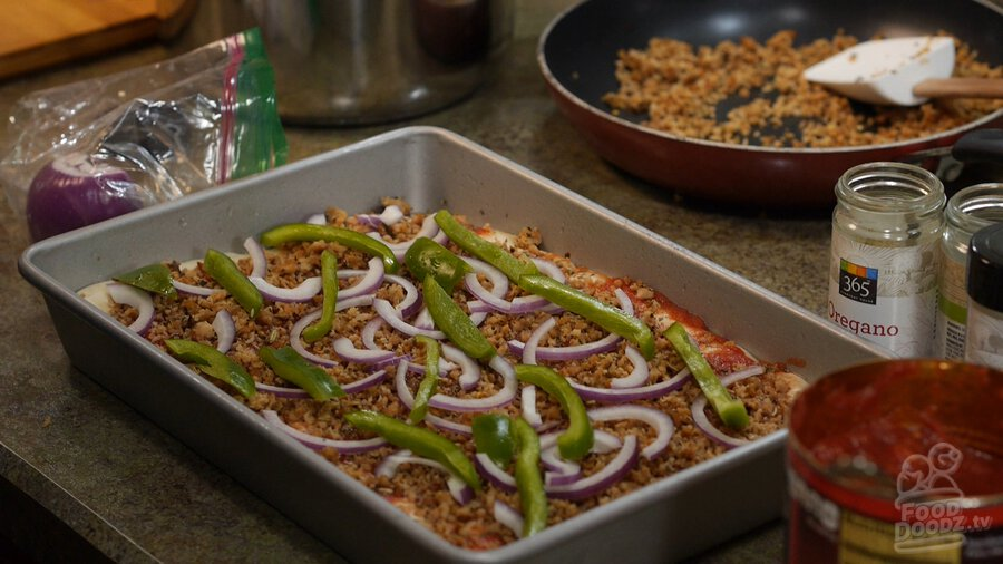 Slices of green peppers and red onion top pizza dough in sheet pan
