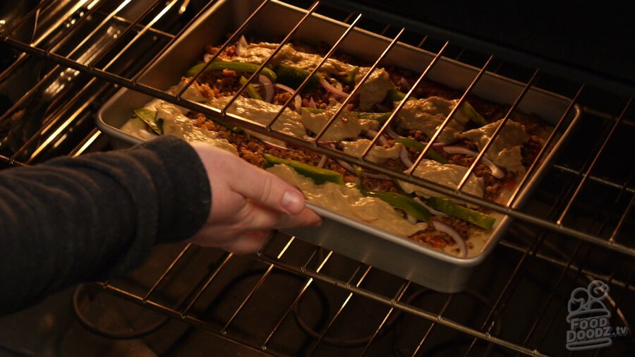 Hand places sheet pan pizza on rack in oven