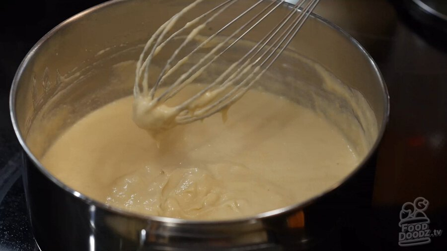 Showing how cashew mixture thickens and starts to clump together on end of whisk