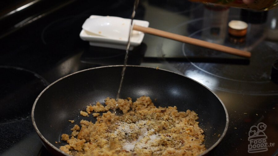 Pouring vinegar into skillet of textured vegetable protein (TVP) sauteing with seasonings