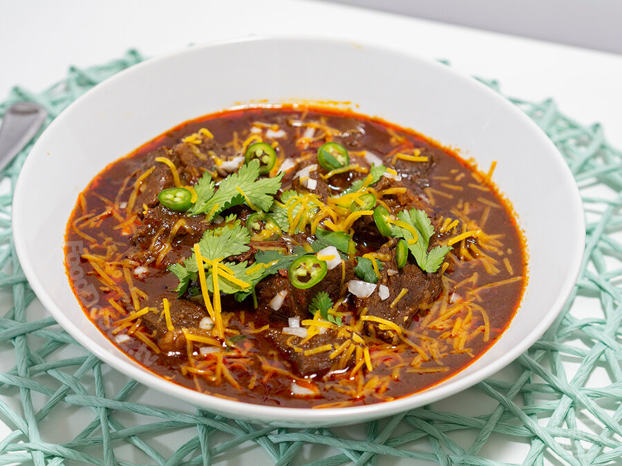 Very large and appetizing bowl of bright red chili with large chunks of beef topped with cilantro, sliced serrano chilies, and cheese