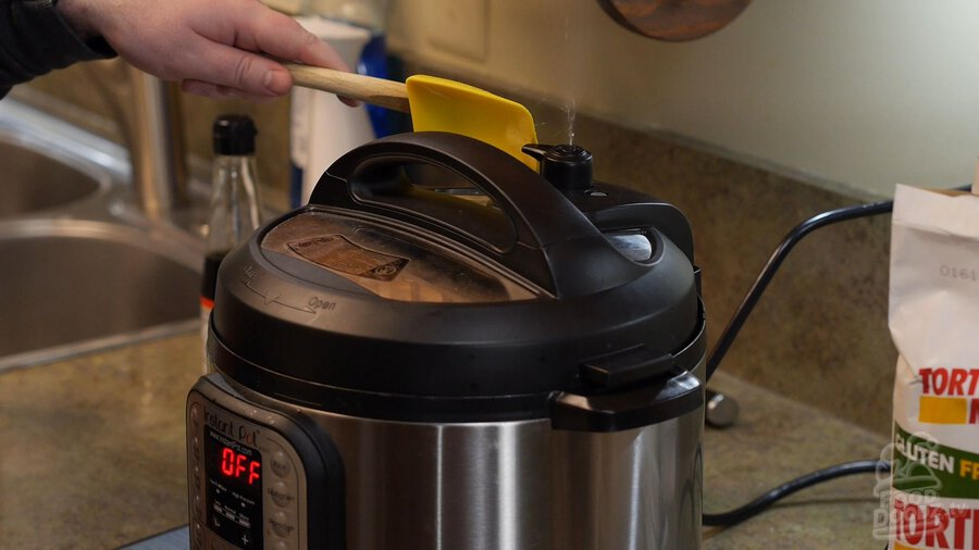 Hand uses spoonula to release pressure valve on Instant Pot