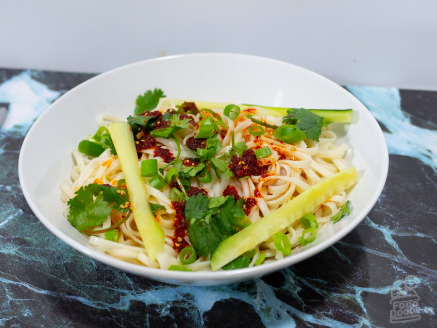 An extremely appetizing bowl of wheat noodles sit on a colorful faux marble place mat. Bright red chili oil, sliced scallions, cilantro, and cucumber sticks top the noodles.