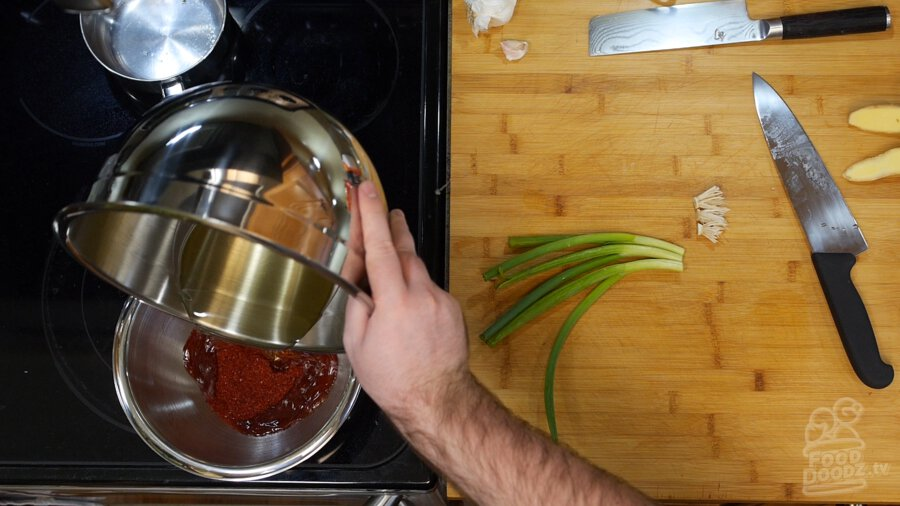 Pouring hot oil over chili flakes