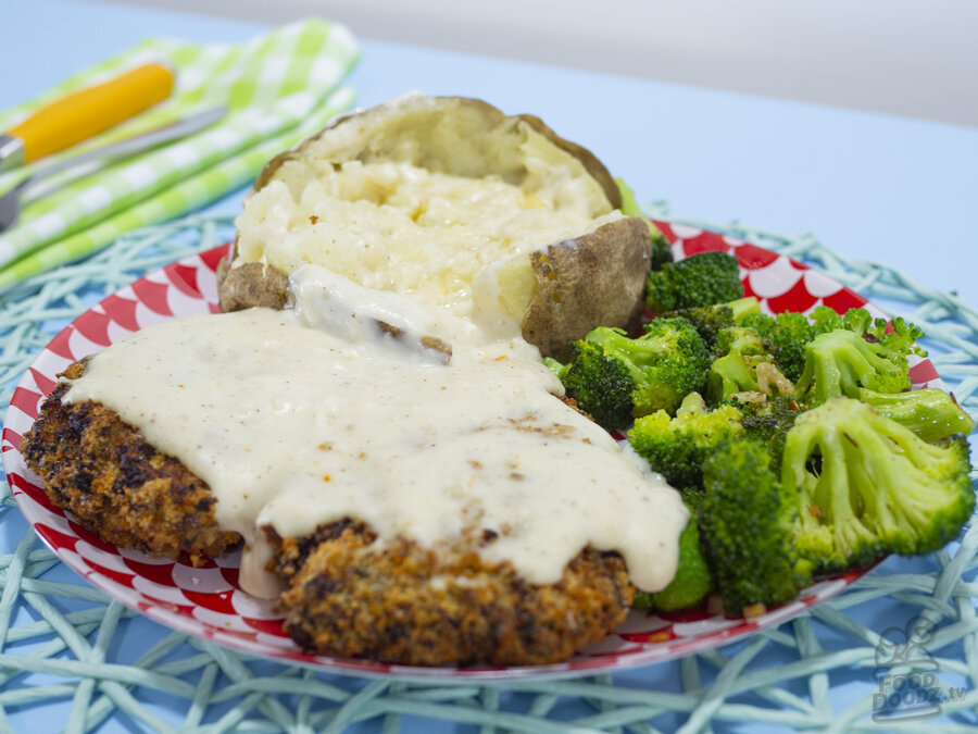 A hearty plate of chicken fried steak covered in white gravy with a baked potato and sauteed broccoli