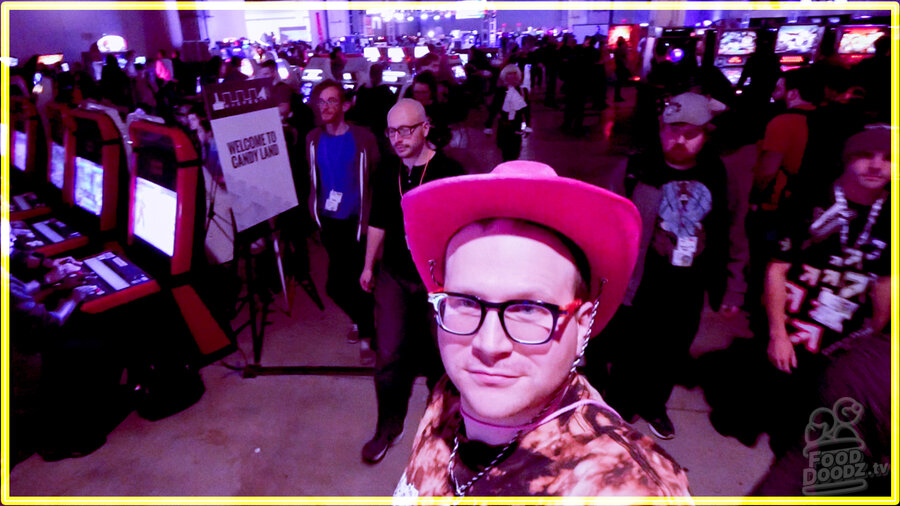 Austin (man) wearing pink cowbow hat looks into the camera while an enormous neon blade runner style arcade is seen behind him