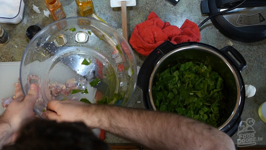 Spinach being added on top of the onions, garlic, ginger, and spices