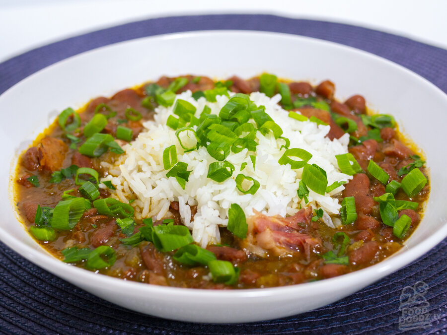 A bountiful bowl of cajun red beans and rice topped with green onions and parsley