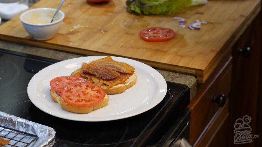Adding tomato to mayoed bread