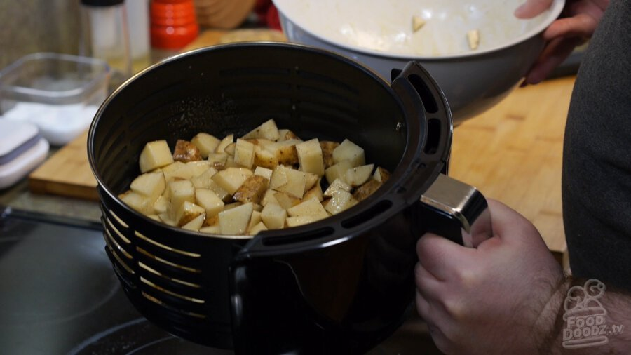 Raw seasoned potatoes in air fryer basket