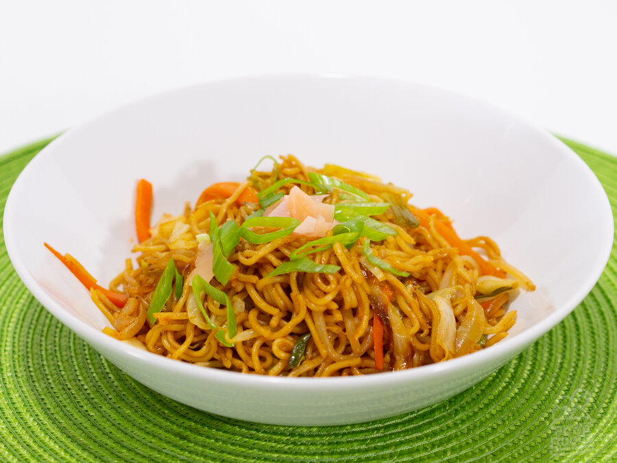 A delectable bowl of vegetable yakisoba piled high and topped with pickled ginger and green onions