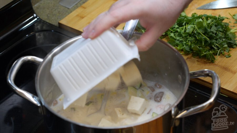 Chopped tofu being added to pot