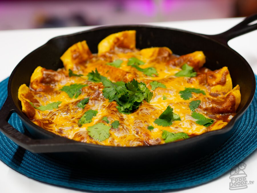 A cast iron skillet full of tex mex cheese and onion enchilada goodness.