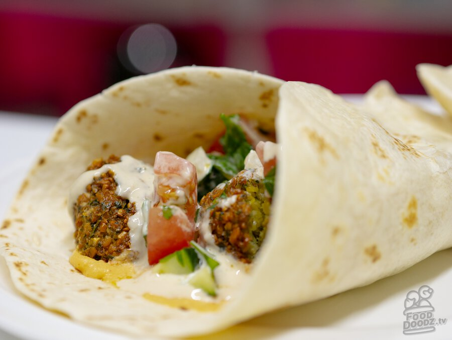 A mouth watering wrap of freshly fried falafel with hummus, cucumber tomato salad, and tahini sauce