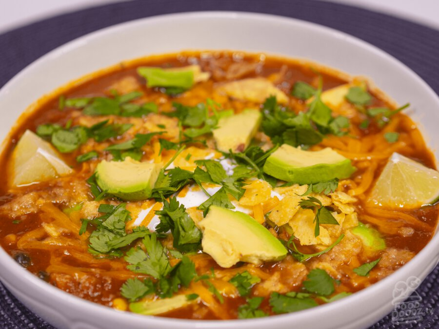 A vibrant bowl of chicken tortilla soup topped with cheese, sour cream, avocado, lime, tortilla chips, and cilantro.