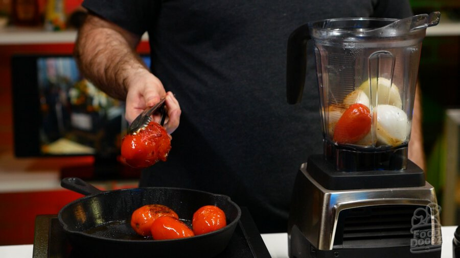 A well charred tomato being removed to a blender