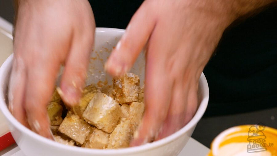 Carefully mixing tofu with hands
