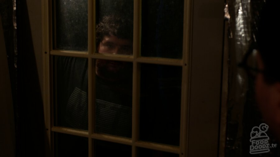Adam standing in darkness knocking on window of door. He is barely illuminated. Austin's head is a dark blob across the right side of the screen.