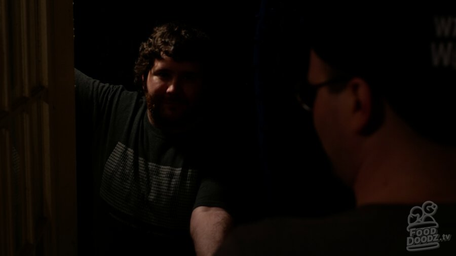 Adam standing in darkness through doorway. He is barely illuminated. He's handing Austin something. Austin's head and shoulders are a dark blob across the right third of screen.