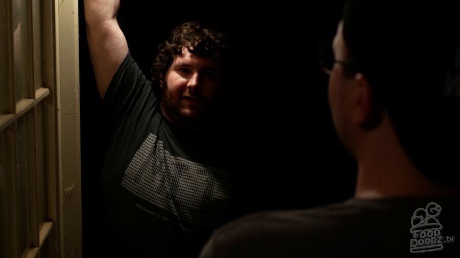 Adam standing in darkness through doorway. He is harshly illuminated from above on one side of his face. Austin's head and shoulders are a dark blob across the right third of screen.
